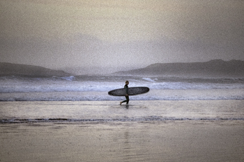 Photograph image of a surfer on the beach