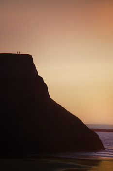 Photograph of a silhouette of a couple on top of a cliff on the beach