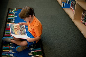 Stock Photo: Student Reading a Book in the Library #2 -Per